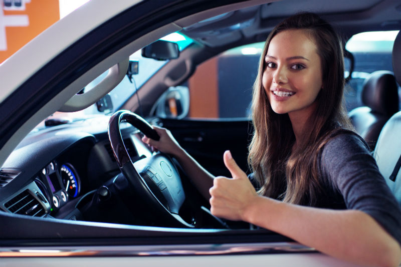 Happy woman in new car